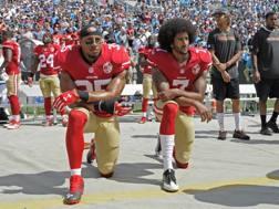 Colin Kaepernick (a destra) inginocchiato per protesta durante l'inno, in una partita del 2016. Ap