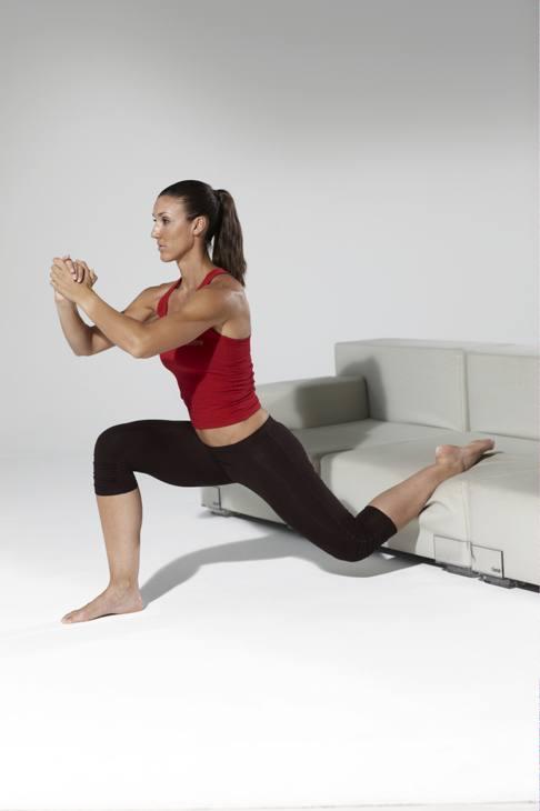 Cosce e glutei. Dalla stazione eretta, appoggiare un piede sul divano, piegare la gamba a terra a 90° e avvicinare il ginocchio opposto al suolo. 3 serie da 10 ripetizioni per lato.