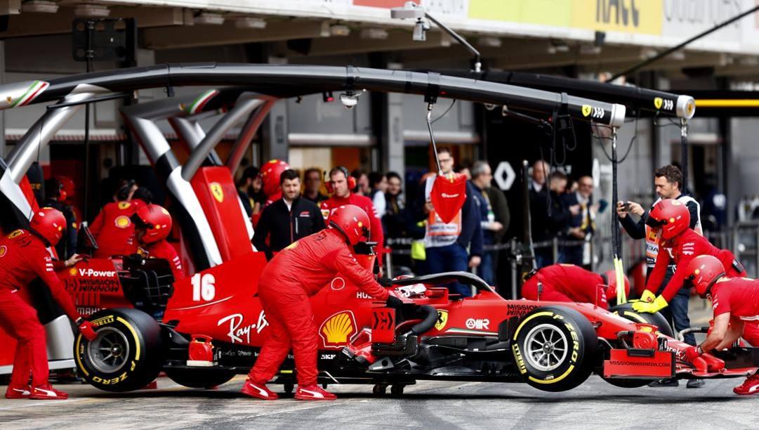 Meccanici al lavoro nei test di Barcellona sulla vettura di Leclerc. Ap