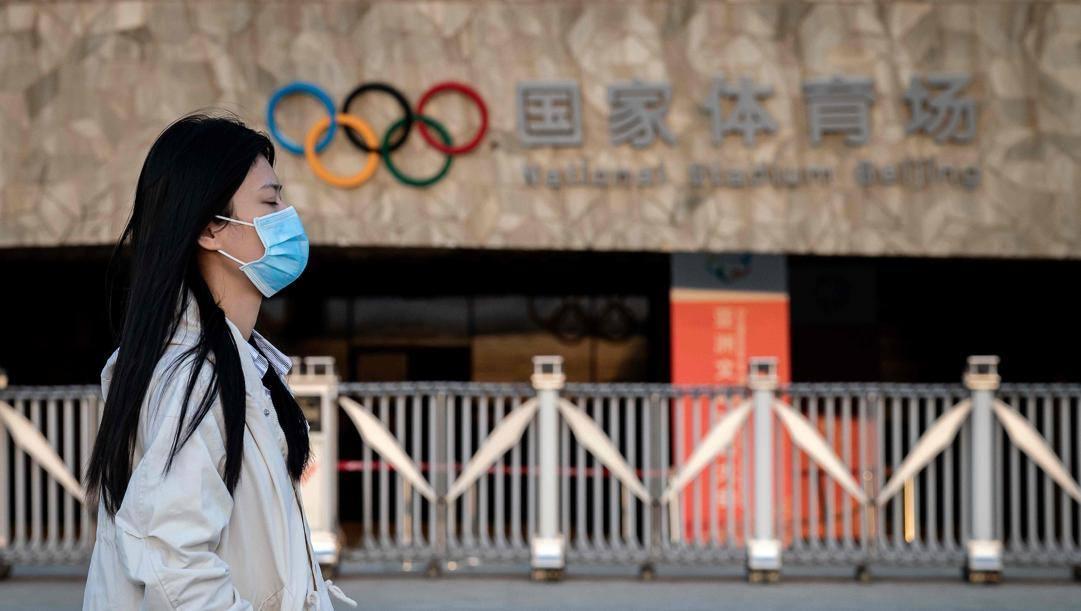 Una donna indossa la mascherina: sullo sfondo, i cinque cerchi. Afp
