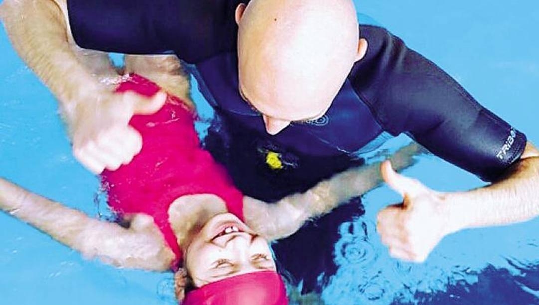 Una bambina in piscina con un istruttore