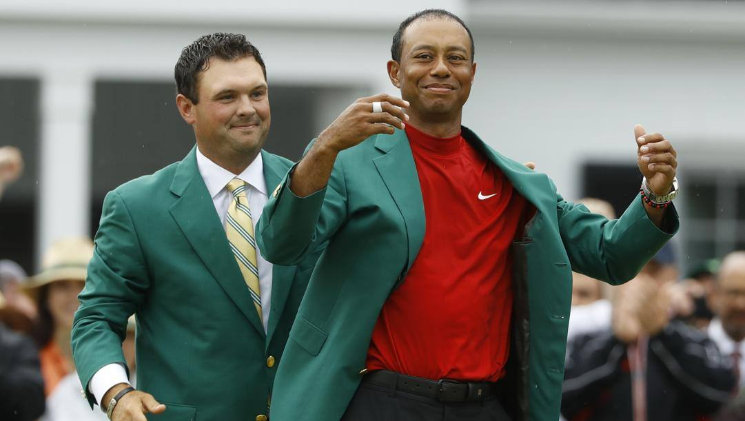 Tiger Woods riceve la giacca verde dal campione 2018 Patrick Reed.