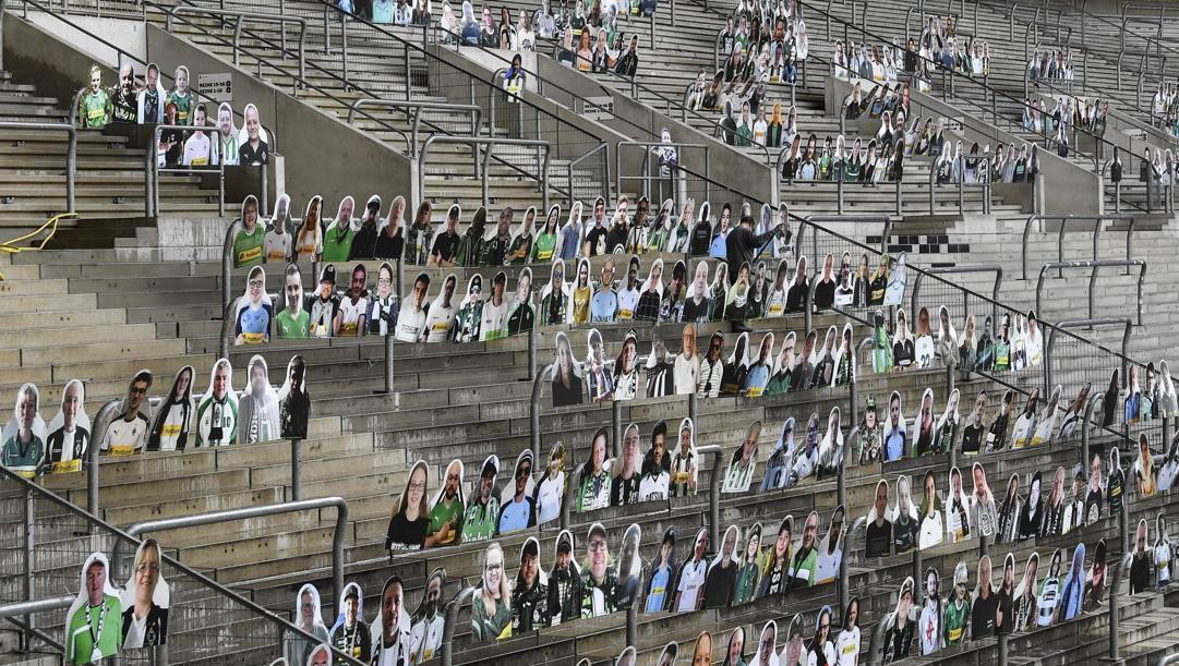 Il Borussia Monchengladbach con le foto dei tifosi sulle gradinate. AP