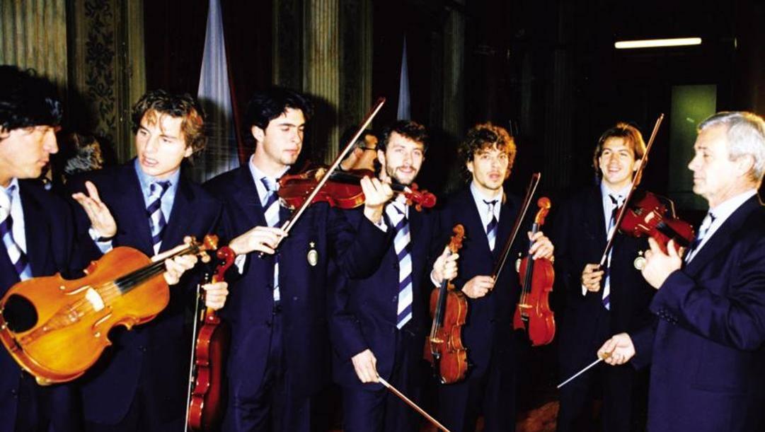 Simoni direttore d'orchestra. Ai violini, da sinistra, Zamorano, Colonnese, Fresi, Ganz, Moriero e Cauet dopo la Coppa Uefa vinta nel '98. Dfp