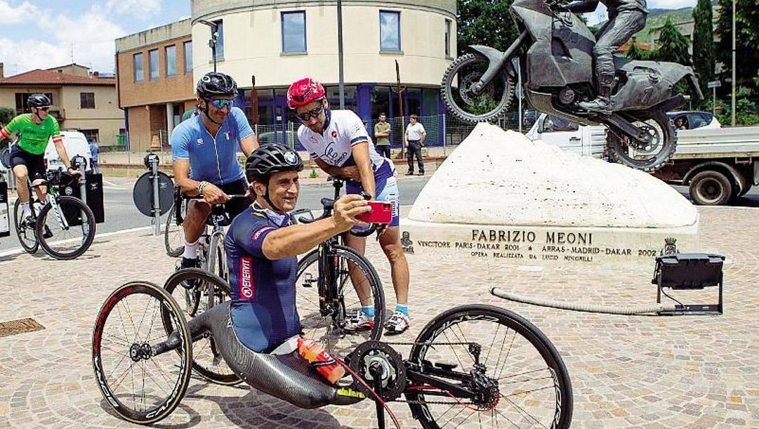 Venerdì, sosta a Castelfiorentino: Alex Zanardi fa un selfie con Daniele Bennati (in azzurro) e Enrico Fabianelli davanti al monumento che ricorda Fabrizio Meoni, vincitore della Dakar 2001 e morto nel 2005