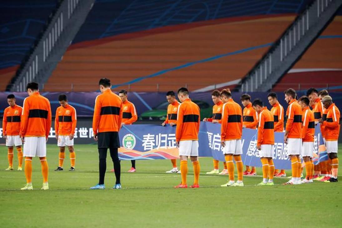 """Testa bassa e striscione bene in vista: così i calciatori del Wuhan Zall sono scesi in campo per la prima giornata del primo campionato cinese post pandemia. Nello striscione un ringraziamento agli """"eroi della pandemia"""". Afp"""