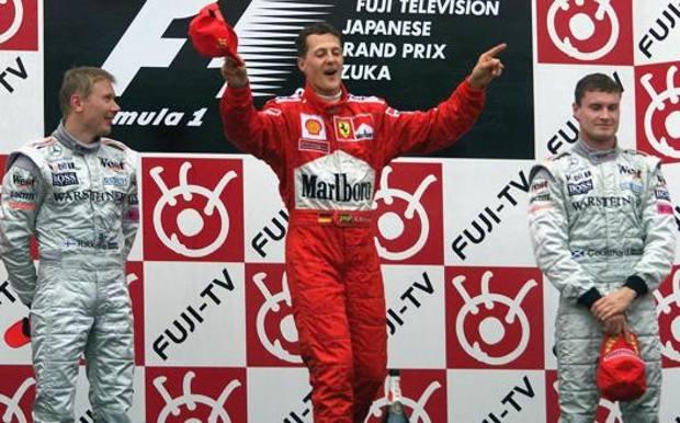"""Schumacher sul podio di Suzuka mentre """"dirige l'orchestra durante l'inno italiano. EPA"""