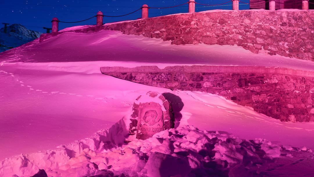La cima dello Stelvio qualche anno fa: in mezzo alla neve,colorata di rosa, con la stele dedicata a Fausto Coppi in bella evidenza