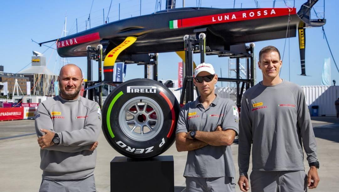 Gli uomini di Luna Rossa e il pneumatico di F1 tricolore all'asta, autografato dal team