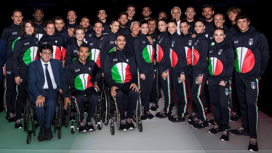 Giorgio Armani in mezzo agli azzurri che indossano le divise preparate per Tokyo e Pchino. Ansa
