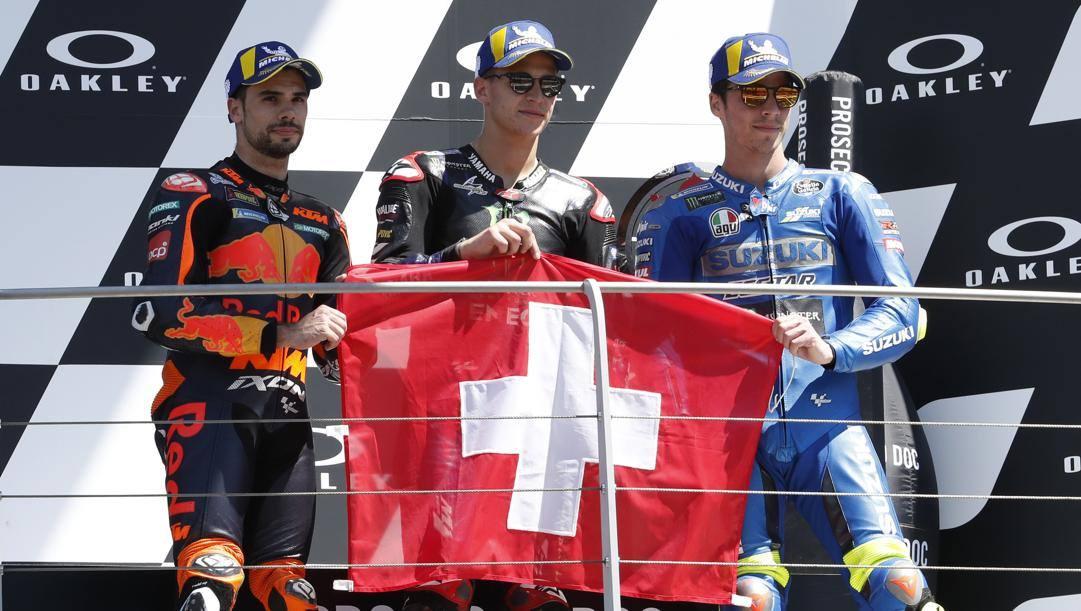 Il podio del Mugello: Fabio Quartararo, Miguel Oliveira e Joan Mir mostrano la bandiera svizzera in ricordo di Jason Dupasquier. Lapresse