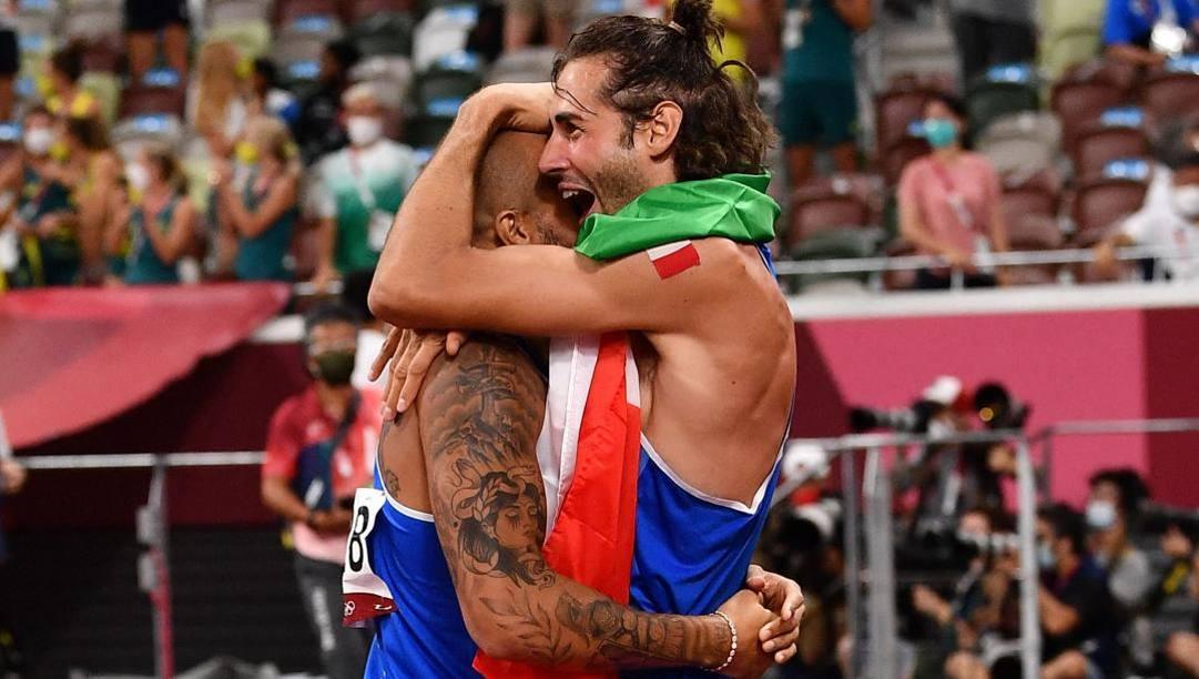 L'abbraccio al traguardo dei 100 metri olimpici. Afp